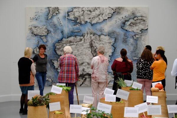 6 bezoekers kijken naar twee schilderijen op de eregalerij van het Rijksmuseum tijdens een prikkelarm museumbezoek