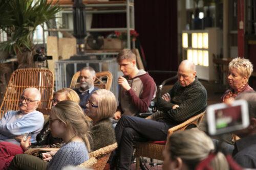 Het publiek luistert naar de muzikant.